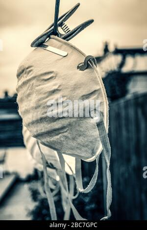 Face protection masks hanging on Clothes line - Stock Photo