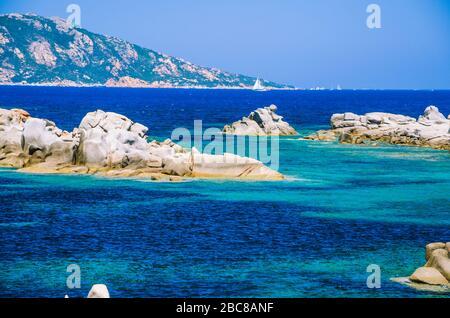 Granite rocks in sea, amazing azure water, white sailboat in background near Porto Pollo, Sardinia, Italy. - Stock Photo