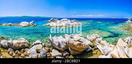 Granite rocks in sea, amazing azure water, white sailboats in background near Porto Pollo, Sardinia, Italy. Banner - Stock Photo