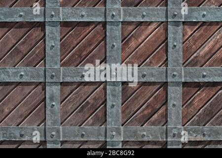 Wooden gate of the castle behind a grating