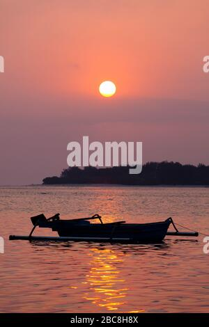 Asia, Indonesia, West Nusa Tenggara, Gili Air, Sunset over Gili Meno with Traditional Outrigger Boat - Stock Photo