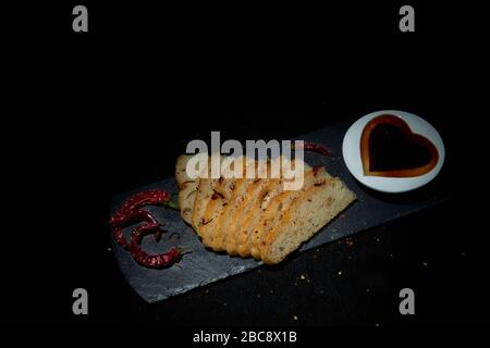 Display of homemade Italian style Focaccia bread with red chillies.  Sliced bread on black slate with balsamic vinegar in heart shape dish a - Stock Photo