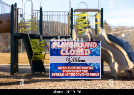 Helena, Montana - March 30, 2020: Playground closed sign with yellow caution tape wrapped around slide & stairs to prevent spread of Coronavirus. - Stock Photo