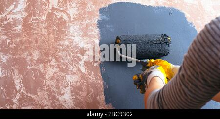 home repair concept. girl paints a wall paint.