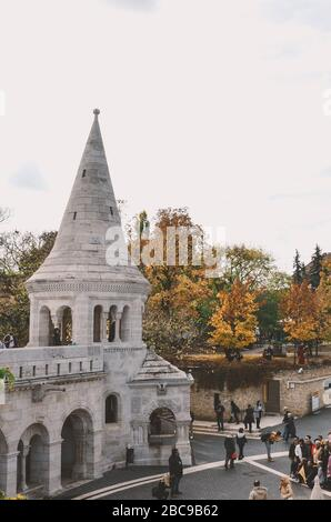Budapest, Hungary - Nov 6, 2019: Tourists sightseeing and taking photos of Fishermans Bastion in the Hungarian capital city. Historical center, autumn trees. Vertical photo. - Stock Photo