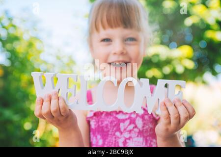 Little toddler - laughing girl in a pink dress holding the words WELCOME in her hands - Stock Photo