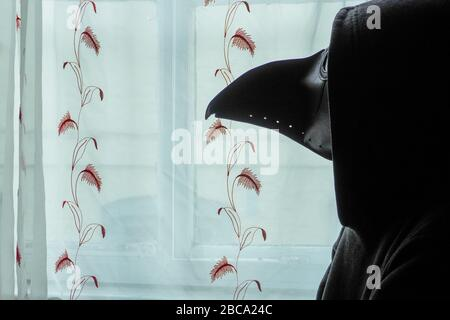 A scary, hooded figure wearing a plague doctor mask, looking out of a window - Stock Photo