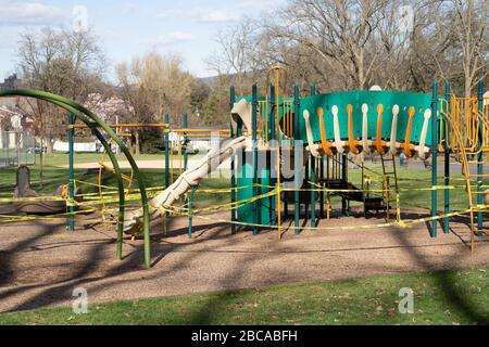 Berks County, Pennsylvania, USA-April 2, 2020: Public playground closed with caution tape so children do not play on equipment to prevent spread of co - Stock Photo