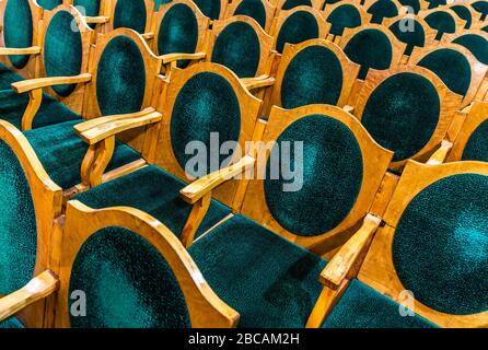 Wooden chairs with green upholstery in the hall.