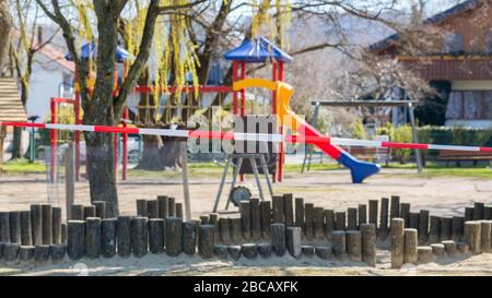 Playground with no kids. Closed off with a red - white striped barrier tape. Forbidden to enter due to the Coronavirus (Covid-19) restrictions.