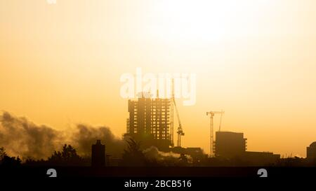 Steam rises above the rooftops as the sun shines through a hazy sky above the west London skyline - Stock Photo