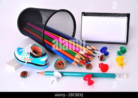 Color pencils, pencil sharpener, business card holder, eraser on white background