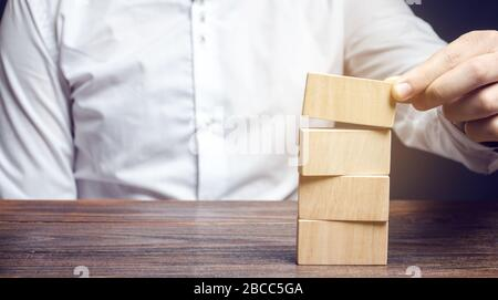 Businessman puts wooden blocks. Management of risks. Business management concept. Planning and strategy. Setting and achieving goals. Performance. Stock Photo