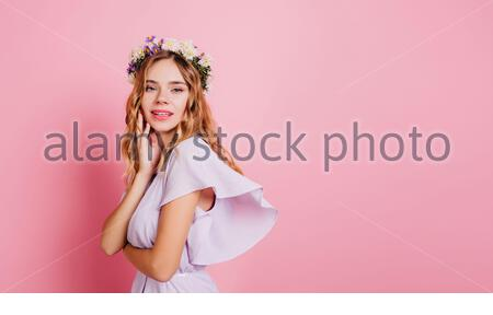 Adorable caucasian woman with blonde hair posing with shy smile. Studio portrait of ecstatic white girl in flower wreath standing beside pink wall. - Stock Photo