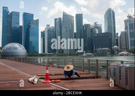 02.04.2020, Singapore, Republic of Singapore, Asia - Worker repairs wooden planks along the waterfront in Marina Bay with the city skyline of the CBD.