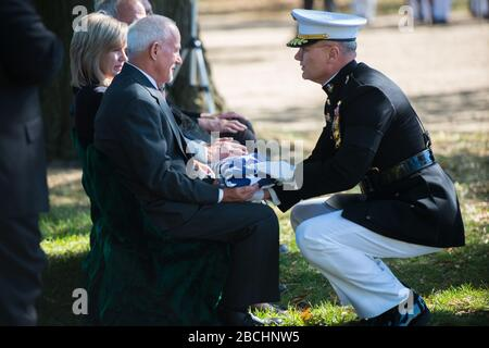 'Bruce Placek receives the American flag from U.S. Marine Corps Brig. Gen. Norman Cooling, director, Office of Legislative Affairs for the Commandant of the Marine Corps, during the graveside service for his uncle, U.S. Marine Corps Cpl. Walter Critchley, in Section 60 of Arlington National Cemetery, Arlington, Va., Oct. 18, 2017.  In November 1943, Critchley was assigned to Company F, 2nd Battalion, 8th Marines, 2nd Marine Division, which landed against stiff Japanese resistance on the small island of Betio in the Tarawa Atoll of the Gilbert Islands, in an attempt to secure the island.  A bat - Stock Photo