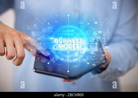 Businessman holding a foldable smartphone with BUSINESS MODEL inscription, new business concept