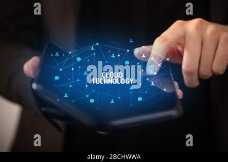 Businessman holding a foldable smartphone with CLOUD TECHNOLOGY inscription, new technology concept