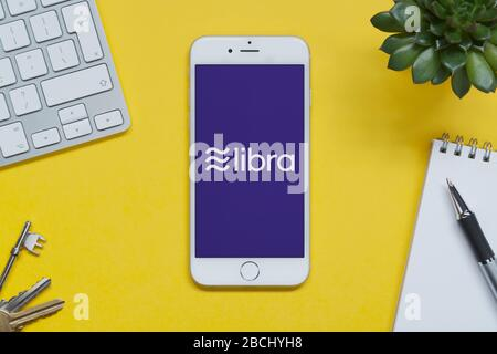 An iPhone showing the Facebook Libra logo rests on a yellow background table with a keyboard, keys, notepad and plant (Editorial use only). - Stock Photo