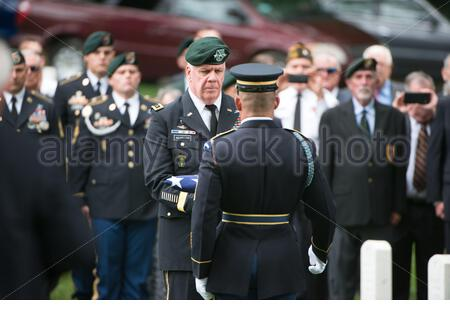 'Lt. Gen. John F. Mulholland Jr., center left, receives the American Flag from U.S. Army First Sgt. Jose Barreiro, center right, to give to the family of U.S. Army Sgt. 1st Class Alan Lee Boyer during Boyer's graveside service in Section 28 of Arlington National Cemetery, June 22, 2016, in Arlington, Va. Boyer, a Green Beret, was listed missing in action during the Vietnam War and his remains were recently identified. (U.S. Army photo by Rachel Larue/Arlington National Cemetery/released); 22 June 2016, 14:24; Graveside service for U.S. Army Sgt. 1st Class Alan Lee Boyer in Arlington National C - Stock Photo