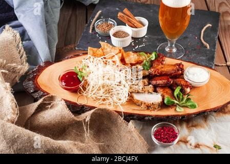 Chicken wings, cheese and breaded fish served with cold beer on a wooden background - Stock Photo