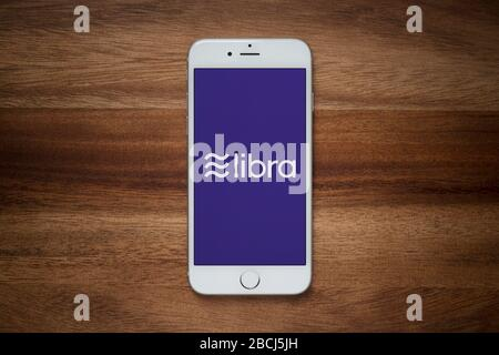 An iPhone showing the Facebook Libra website rests on a plain wooden table (Editorial use only). - Stock Photo