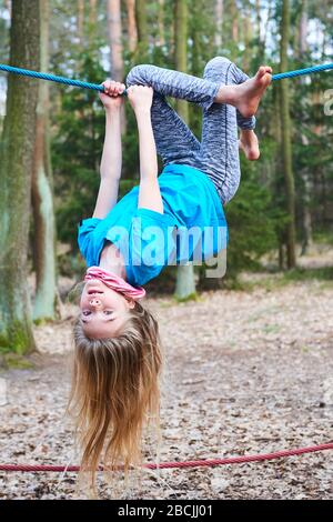 Young child girl hanging on rope upside down on playground in park - Stock Photo