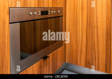 Modern wooden brown orange kitchen features cabinets with microwave oven on lower side and buttons closeup