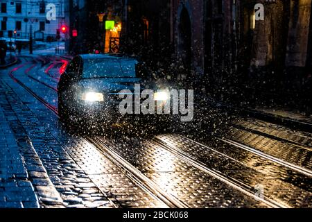 Lviv, Ukraine old town in Lvov at night with snow weather road and car in alley with reflection of headlights and snowflakes in winter - Stock Photo