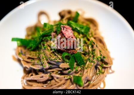 Traditional Japanese white plate with black background and vegetable dish with soba buckwheat noodles, seaweed, green onion negi and umeboshi pickled