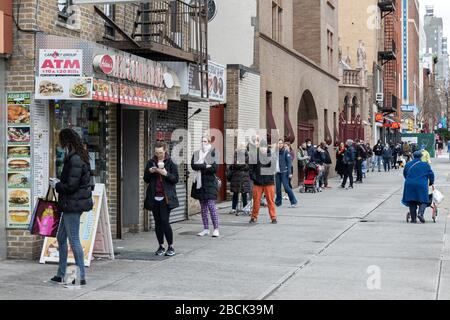 Socially-distanced shoppers wait in line for entry to a Trader Joe's in Manhattan, New York on April 04, 2020. The spread of Covid-19, coronavirus, ha - Stock Photo