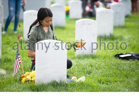 'Audrey Hsieh visits the gravesite of U.S. Marine Corps Staff Sgt. Donald C. May Jr. in Section 60 of Arlington National Cemetery for Memorial Day, May 30, 2016, in Arlington, Va. Hsieh was a T.A.P.S. mentor to May's son's. (U.S. Army photo by Rachel Larue/Arlington National Cemetery/released); 30 May 2016, 10:31; Memorial Day in Arlington National Cemetery; Arlington National Cemetery; ' - Stock Photo