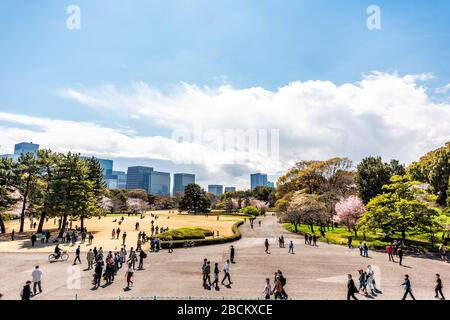 Tokyo, Japan - April 1, 2019: View from site of Edo Castle keep at Imperial palace national gardens park with cityscape skyline of modern skyscrapers - Stock Photo