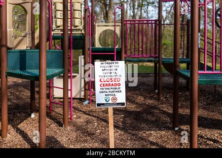 Herndon, USA - March 24, 2020: Sign in children's playground in Virginia city for park closure, facility closed to public due to covid-19 to stop spre - Stock Photo