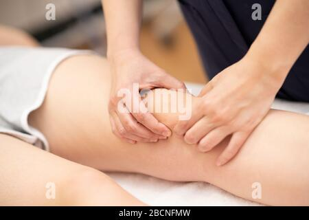 Physiotherapist woman doing a treatment on a woman's knee. Stock Photo