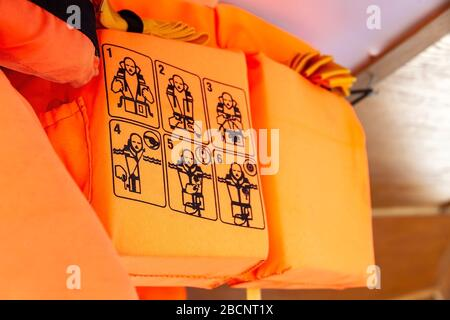 Orange life vests on a ship, closeup on the use instructions, detail How to put on, putting on a life jacket, shallow dof. Personal flotation device - Stock Photo
