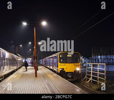 Northern Rail class 150 sprinter trains 150135 +150139 waiting to depart from Wigan North western railway station early in the morning - Stock Photo