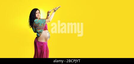 Pregnant happy woman in Indian sari with mehendi tattoo painted with henna on belly, fun fooling over yellow background, panoramic mock-up with space - Stock Photo