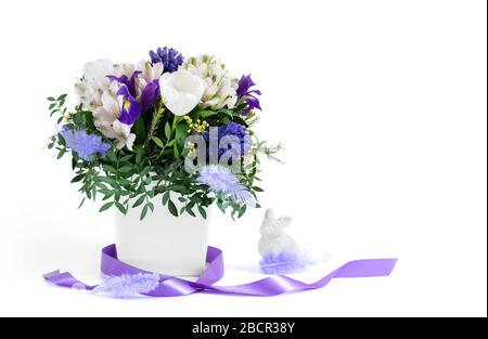 Easter composition. Spring flowers with feathers, purple ribbon and Easter Bunny on a white background. Copy space. Side view.
