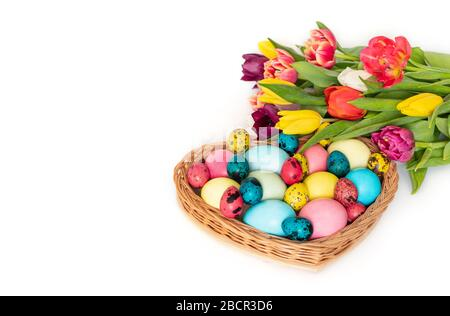 Easter colorful eggs and a bouquet of spring tulip flowers on a white background. Horizontal orientation. Copy space.