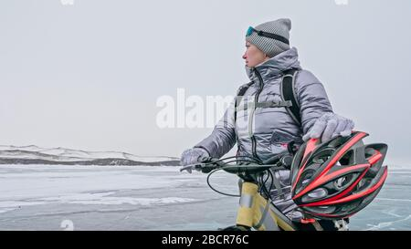 Woman stands near her bike on ice. The girl cyclist stopped to r - Stock Photo
