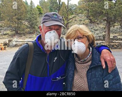 A middle-aged couple wearing dust masks as they leave their home in central Oregon for a grocerly shopping trip into the city of Bend, Oregon. - Stock Photo