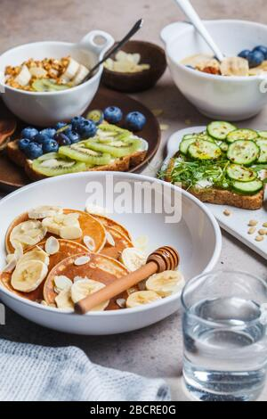 Healthy varied vegetarian breakfast table. Oatmeal with fruits, chia pudding, pancakes with banana and honey and toasts with fruits, vegetables and cr - Stock Photo