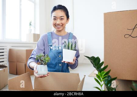 Portrait of young Asian woman packing plants to cardboard boxes and smiling at camera while moving to new house or apartment, copy space