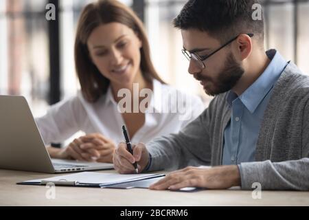 Close up handsome businessman signing partnership agreement concept.