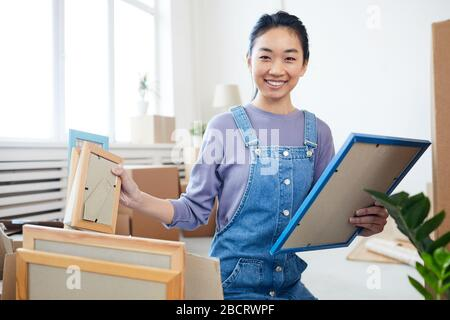 Portrait of young Asian woman packing boxes and smiling at camera excited for moving to new house or apartment, copy space - Stock Photo