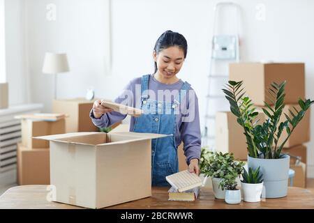 Waist up portrait of young Asian woman packing or unpacking cardboard box and smiling happily while moving into new home, copy space