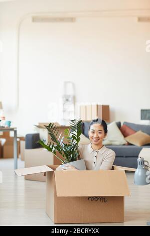 Vertical portrait of young Asian woman sitting in box and holding plant while moving in to new house or apartment, copy space