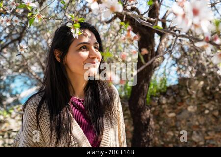 Young woman enjoying the view and the sunlight on her face under Plum tree with blossoms - Stock Photo