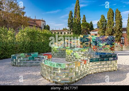 A curved wall of coloured glass blocks created by Pae White named Qwalala on the island of San Giorgio Maggiore ,Venice ,Italy - Stock Photo